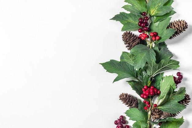 Decorazioni natalizie, ramo con bacche rosse, foglie verdi e coni di abete con spazio per il testo su sfondo bianco