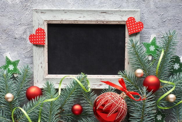 Decorazioni natalizie rosse e verdi: ramoscelli di abete, bacche e palline di natale su cemento grigio,