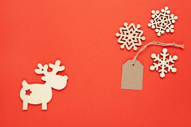 Decorazioni natalizie, tre piccoli fiocchi di neve in legno, etichetta artigianale, cervo su sfondo rosso brillante.
