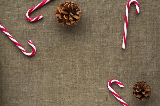 Decorazioni natalizie: vista dall'alto di bastoncini di zucchero e coni su sfondo di tessuto di lino con spazio libero