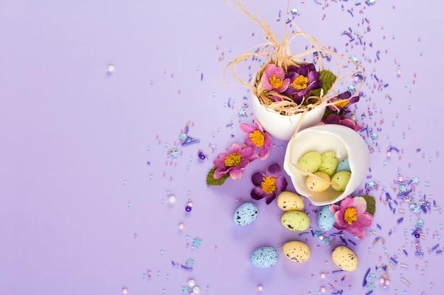 Decorazioni pasquali in colori pastello. uova di pasqua, caramelle, dolci, fiori e gusci d'uovo.