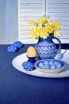 Decorazioni pasquali nei classici colori blu e giallo. uovo arancione con pois e fiore giallo fresia, vaso in ceramica tradizionale, brocca e piatto sulla tovaglia di lino blu. interior design a molla.