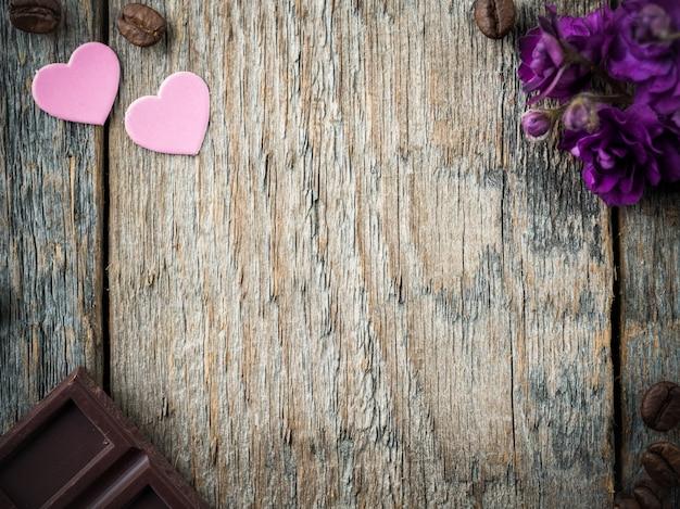 Decorazioni per cuori di carta di san valentino, violette e caffè al cioccolato su fondo di legno rustico.