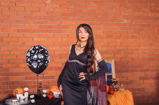 Decorazioni per la casa di halloween con ragni e secchio di zucca per dolcetto o scherzetto. bella ragazza sexy in costume di strega