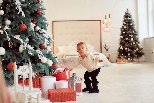 Decorazioni per le vacanze invernali colori caldi. la bella bambina gioca con le scatole attuali