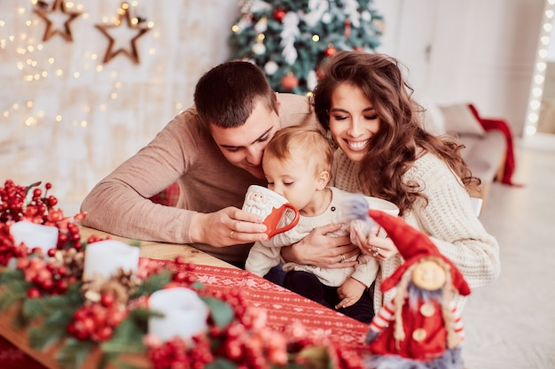 Decorazioni per le vacanze invernali colori caldi. ritratto di famiglia. mamma, papà e la loro piccola figlia