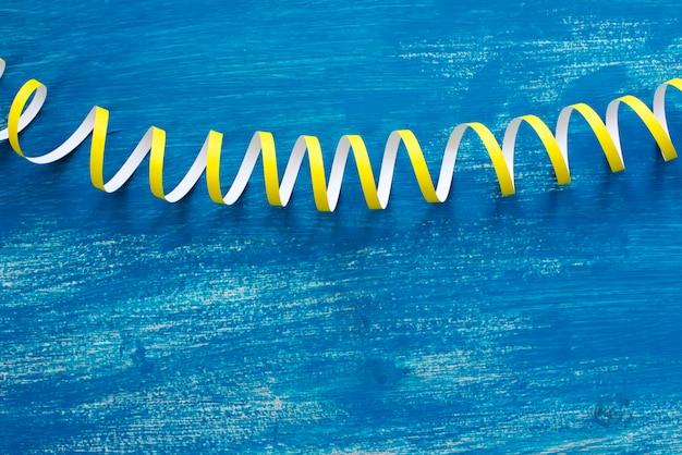 Defocus è un'immagine dettagliata delle serpentine variopinte delle stelle filanti su un'annata blu di legno