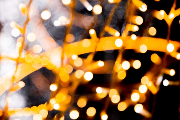 Defocused e sfocato molti tondo luce gialla su sfondo nero di natale