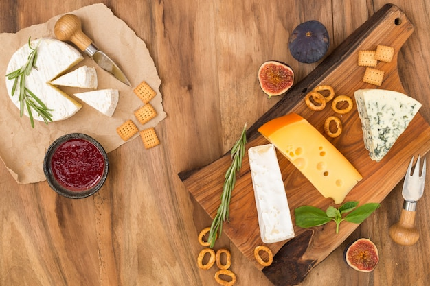 Degustazione del piatto di formaggi con erbe e frutti sul tavolo di legno