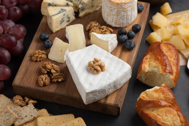 Degustazione di formaggi su un piatto di pietra scura.