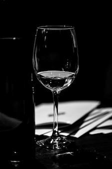 Degustazione di vini sul tavolo di legno c'è un bicchiere di vino splendidamente illuminato. accanto al secchio per rinfrescare vini e brochure presentati ai campioni della mostra. bw.