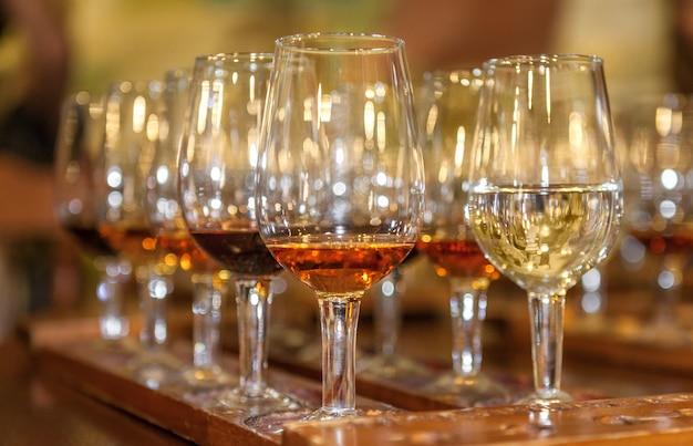 Degustazione di vino rosso e bianco. un vassoio con gli occhiali. avvicinamento
