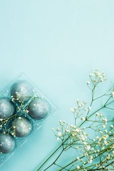 Delicate uova di pasqua blu tra i fiori di gypsophila su sfondo blu.