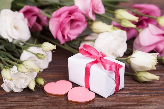 Delicati eustomams bianchi e rosa su uno sfondo di legno scuro. avvicinamento. san valentino. carta festiva