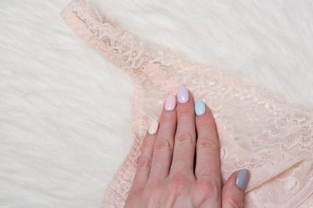 Delicato reggiseno di pizzo beige in mano femminile. disteso. lingerie di moda.