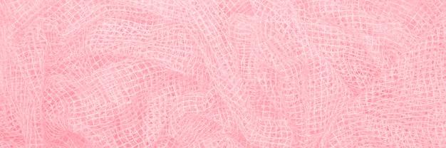 Delicato tessuto sgualcito, piccola bandiera a trama quadrata di un bel colore rosa