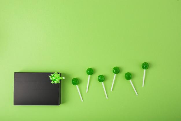 Delicious lecca-lecca con scatola nera su sfondo verde