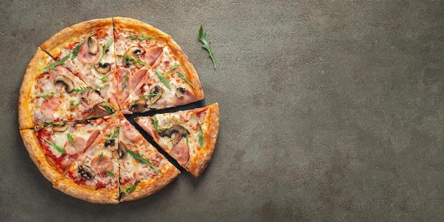 Delicious pizza calda in una scatola con prosciutto.