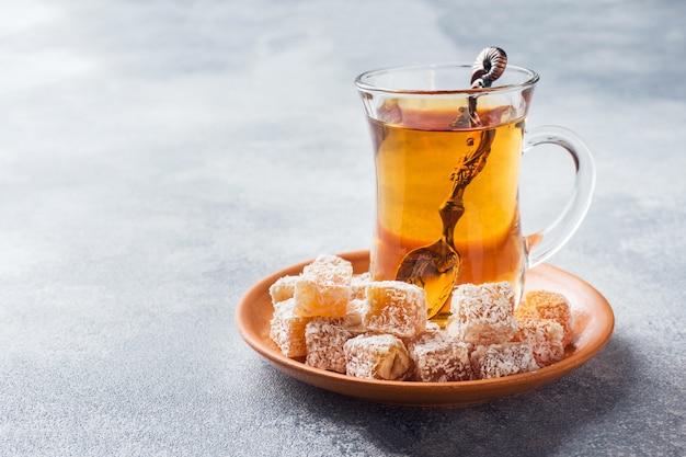 Delizia turca con nocciola in ciotola di metallo scolpita e tè in tazza di vetro