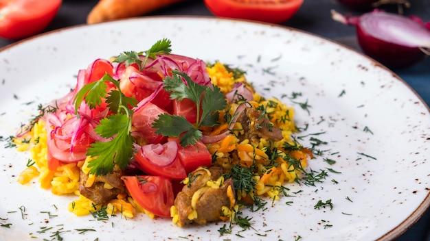 Deliziosa carne pilau, pomodori e cipolle. cibo uzbeko. avvicinamento