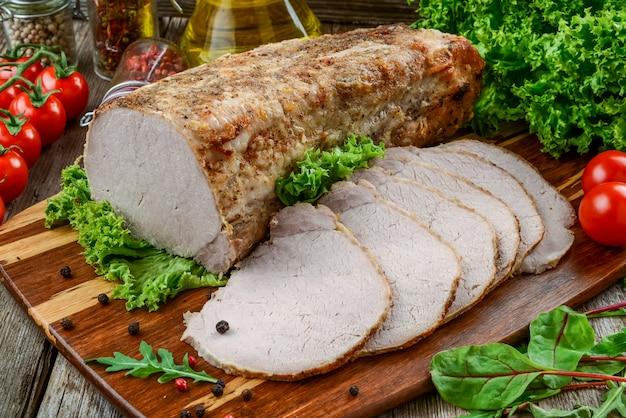Deliziosa carne speziata. carne piccante al forno con peperoncino. pezzo di carne al forno con spezie e verdure sul tavolo.