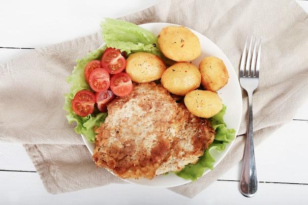 Deliziosa cena con bistecche, patate lesse e insalata
