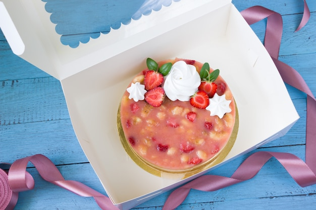 Deliziosa cheesecake con fragole e banana, scatola di consegna bianca, tavola di legno blu