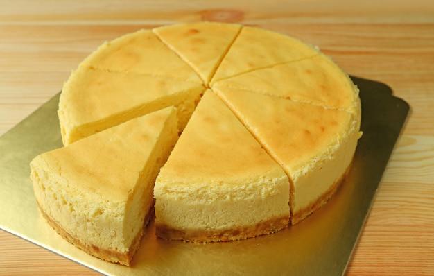 Deliziosa cheesecake cremosa al forno con un pezzo tagliato da tutta la torta