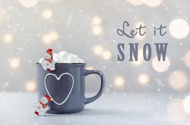 Deliziosa cioccolata calda con marshmallow e piccoli pupazzi di neve su sfondo grigio pietra