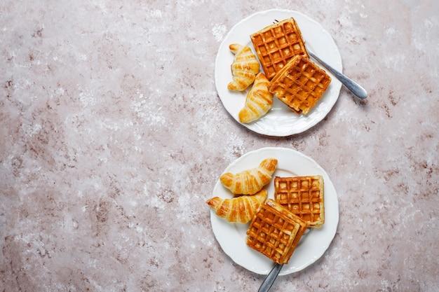 Deliziosa colazione con caffè, succo d'arancia, waffle, cornetti, marmellata, pasta di noci alla luce, vista dall'alto