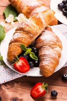 Deliziosa colazione con croissant freschi e frutti di bosco maturi su fondo in legno vecchio