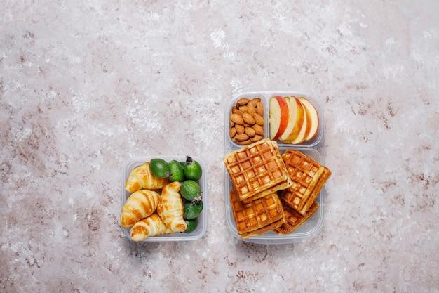 Deliziosa colazione con mandorle, fette di mele rosse, waffle, cornetti su scatola di plastica per il pranzo alla luce