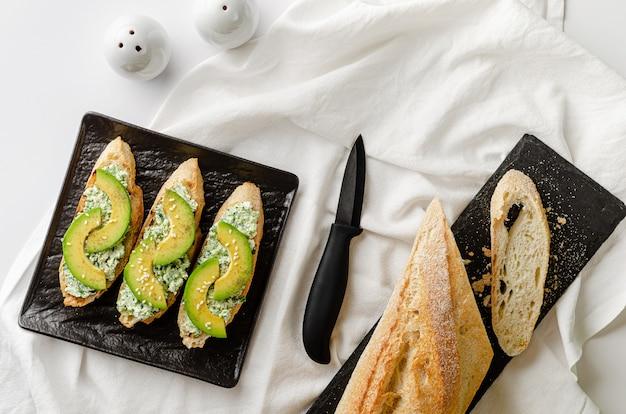 Deliziosa colazione con sandwich aperti a base di baguette, ricotta, spinaci e avocado sulla banda nera sul tavolo bianco