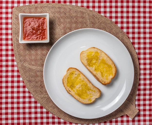 Deliziosa colazione mediterranea composta da toast con olio e pomodoro e un caffè, servita su una tovaglia a quadri vintage e un tovagliolo di tela. .