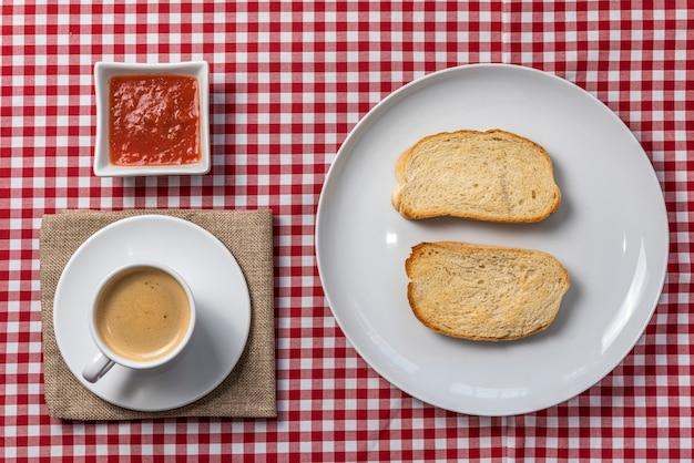 Deliziosa colazione mediterranea composta da toast con pomodoro e caffè, servita su una tovaglia scozzese vintage e un tovagliolo di tela. .