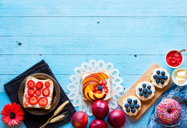Deliziosa colazione sana, panini con diversi ripieni, formaggio, banana, fragola, pesca, burro, mirtillo, su uno sfondo di legno diverso.