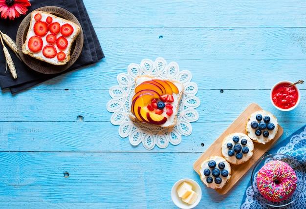 Deliziosa colazione sana, tramezzini alla frutta con ripieni diversi, formaggio, banana, fragola, pesca, burro, mirtillo, su uno sfondo in legno diverso.