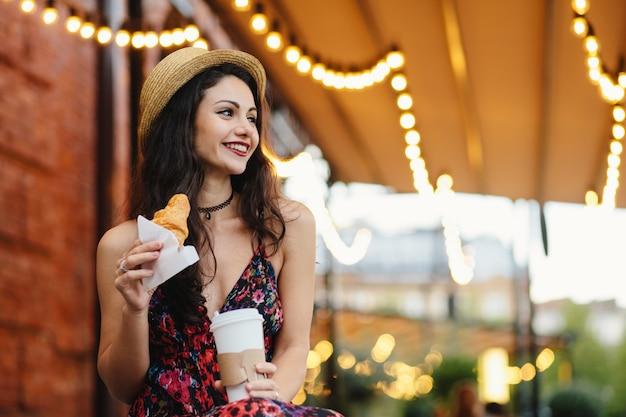 Deliziosa donna bruna con aspetto piacevole che indossa cappello estivo e abito tenendo croissant