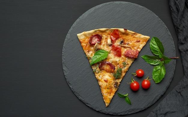 Deliziosa fetta di pizza triangolare con salsicce affumicate, funghi, pomodori, formaggio e foglie di basilico