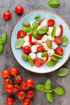 Deliziosa insalata caprese con pomodorini maturi e mini palline di mozzarella con foglie di basilico fresco