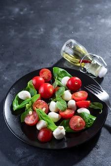 Deliziosa insalata caprese con pomodorini maturi e mini palline di mozzarella