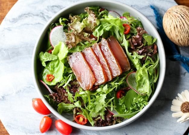 Deliziosa insalata di tonno, tonno bistecca e insalata fresca su un piatto