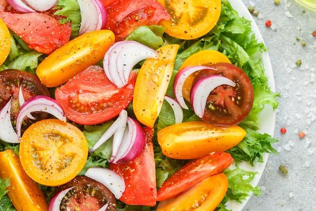 Deliziosa insalata estiva di pomodori maturi colorati (gialli, rossi e neri)