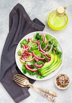 Deliziosa insalata leggera vegetariana di lattuga, radicchio, cipolla rossa e avocado con spezie