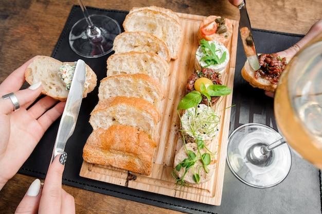 Deliziosa pasta e salsa tartara con fette di pane bianco servita nel piatto di legno