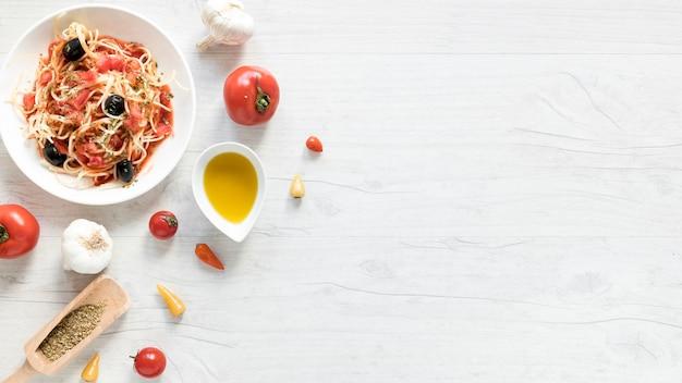 Deliziosa pasta spaghetti sul piatto; pomodoro fresco; ciotola di olio d'oliva ed erbe sulla scrivania in legno