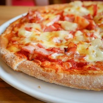 Deliziosa pizza alla hawaiiana in stile rustico a base di ananas fresco, prosciutto e mozzarella