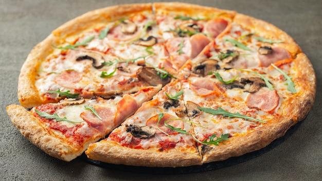 Deliziosa pizza calda con prosciutto e funghi prataioli.