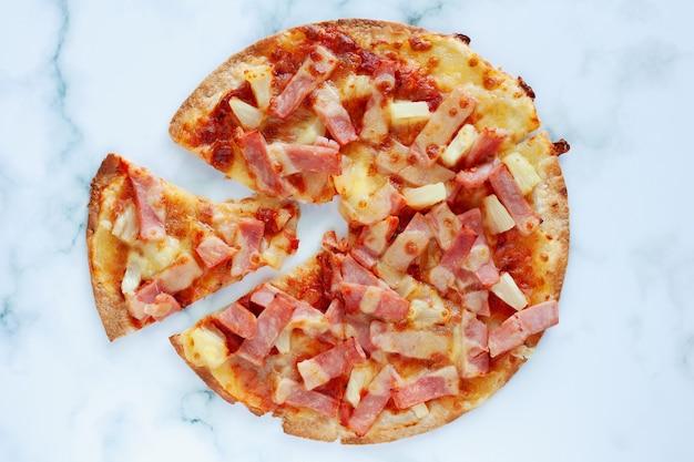 Deliziosa pizza con ananas, fetta di prosciutto, fetta di pancetta, mozzarella, salsa di pizza su sfondo di marmo bianco