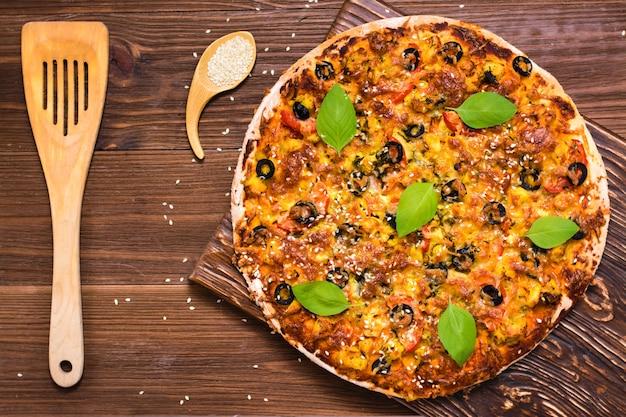 Deliziosa pizza fresca con pollo, pomodori, formaggio e olive nere